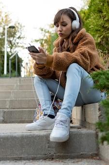 Portret van een jonge studentenmeisje, zittend op de trap. muziek luisteren.