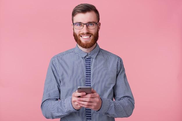 Portret van een jonge succesvolle bebaarde man in een gestreept shirt en bril, glimlacht breed en houdt een smartphone in zijn handen.