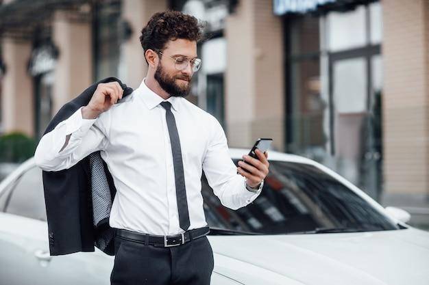 Portret van een jonge, succesvolle, knappe man in een pak op de achtergrond van een nieuwe witte auto, die post op zijn smartphone leest