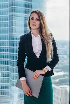 Portret van een jonge succesvolle zakenvrouw die in haar kantoor tegen het raam staat.