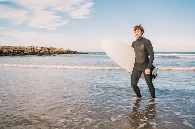 Portret van een jonge surfer die het water verlaat met een surfplank onder zijn arm. sport en watersport concept.