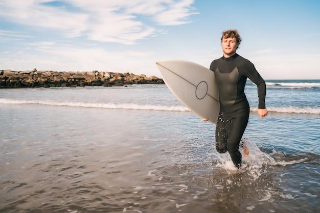Portret van een jonge surfer die het water verlaat met een surfplank onder zijn arm