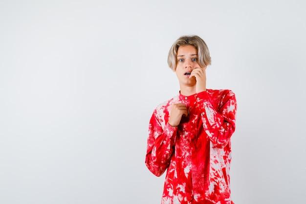Portret van een jonge tienerjongen die de hand op de wang in het shirt houdt en er bang vooraanzicht uitziet
