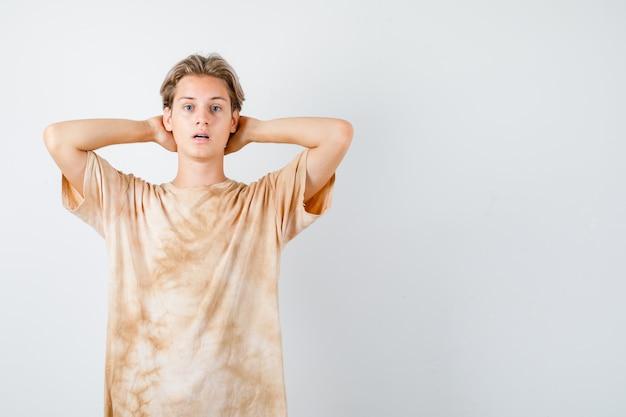 Portret van een jonge tienerjongen die de handen achter het hoofd in een t-shirt houdt en verbijsterd vooraanzicht kijkt