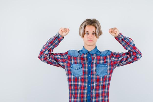 Portret van een jonge tienerjongen die de spieren van de armen in een geruit hemd laat zien en er zelfverzekerd vooraanzicht uitziet