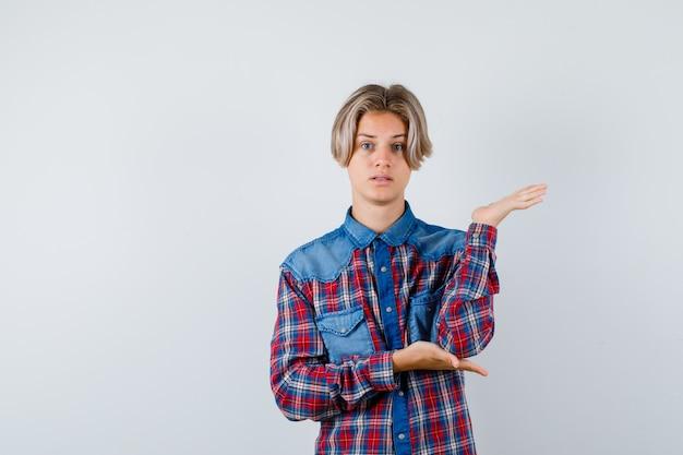 Portret van een jonge tienerjongen die doet alsof hij iets vasthoudt in een geruit overhemd en een verbaasd vooraanzicht kijkt