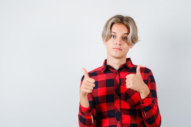 Portret van een jonge tienerjongen die dubbele duimen laat zien in een geruit overhemd en er blij uitziet