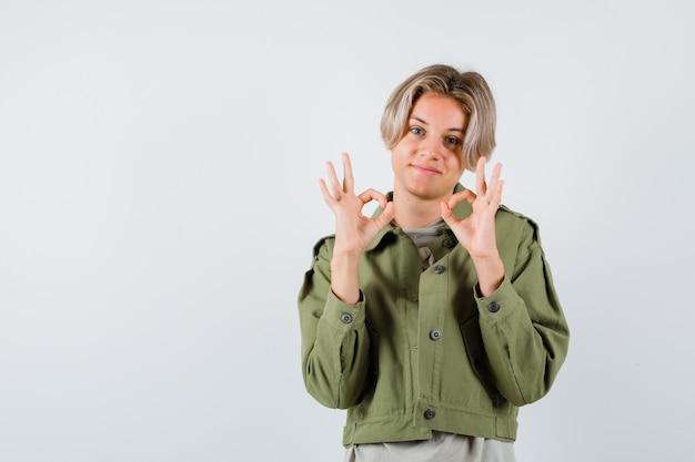 Portret van een jonge tienerjongen die een goed teken in een groen jasje toont en er vrolijk vooraanzicht uitziet