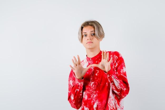 Portret van een jonge tienerjongen die een overgavegebaar in een overhemd toont en een angstig vooraanzicht kijkt