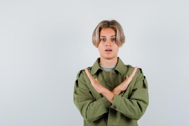 Portret van een jonge tienerjongen die een stopgebaar toont in een groen jasje van het t-leger en een bang vooraanzicht ziet