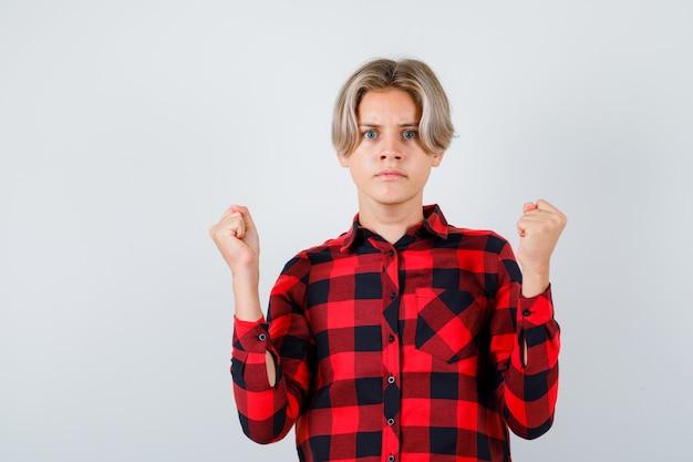 Portret van een jonge tienerjongen die een winnaargebaar toont in een geruit overhemd en er hatelijk vooraanzicht uitziet