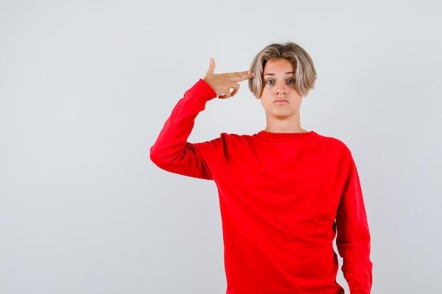 Portret van een jonge tienerjongen die een zelfmoordgebaar in een rode trui toont en een verbaasd vooraanzicht kijkt