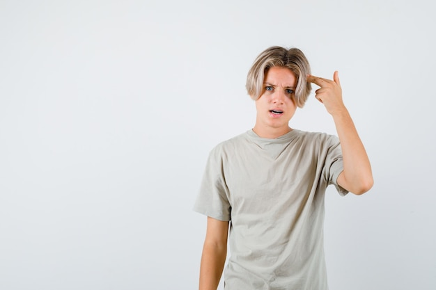 Portret van een jonge tienerjongen die een zelfmoordgebaar in een t-shirt toont en er nerveus vooraanzicht uitziet