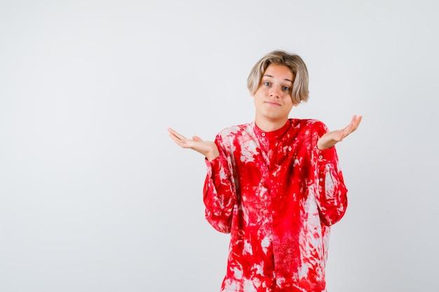 Portret van een jonge tienerjongen die hulpeloos gebaar in overhemd toont en verward vooraanzicht kijkt