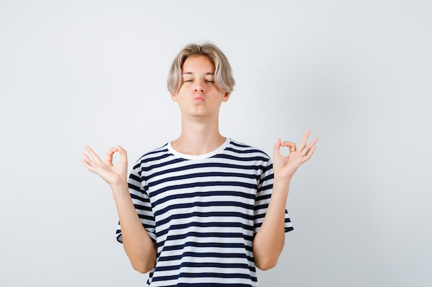 Portret van een jonge tienerjongen die mudra-teken toont, ogen dicht houdt, lippen pruilt in gestreept t-shirt en er ontspannen vooraanzicht uitziet
