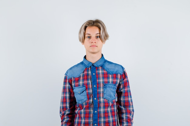 Portret van een jonge tienerjongen die naar de camera in een geruit overhemd kijkt en er intelligent vooraanzicht uitziet