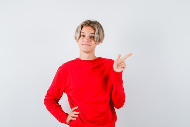 Portret van een jonge tienerjongen die naar de rechterbovenhoek wijst in een rode trui en er vrolijk vooraanzicht uitziet