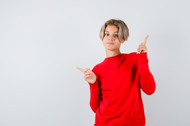 Portret van een jonge tienerjongen die naar links en rechts wijst in een rode trui en er zelfverzekerd uitziet