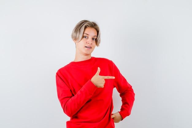 Portret van een jonge tienerjongen die naar rechts in een rode trui wijst en zelfverzekerd vooraanzicht kijkt