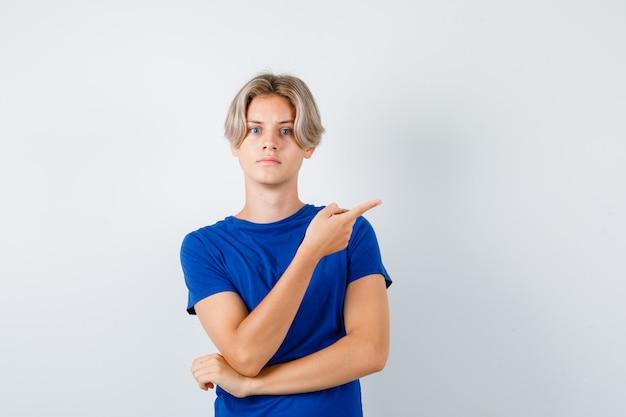 Portret van een jonge tienerjongen die naar rechts wijst in een blauw t-shirt en er nerveus vooraanzicht uitziet