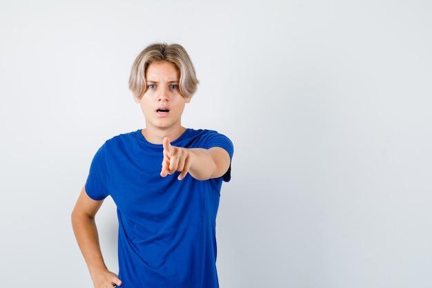Portret van een jonge tienerjongen die naar voren wijst in blauw t-shirt en perplex vooraanzicht kijkt