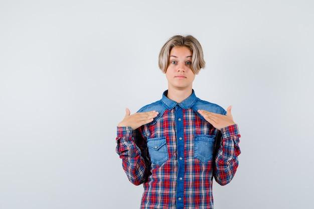 Portret van een jonge tienerjongen die naar zichzelf wijst in een geruit overhemd en een verbaasd vooraanzicht kijkt