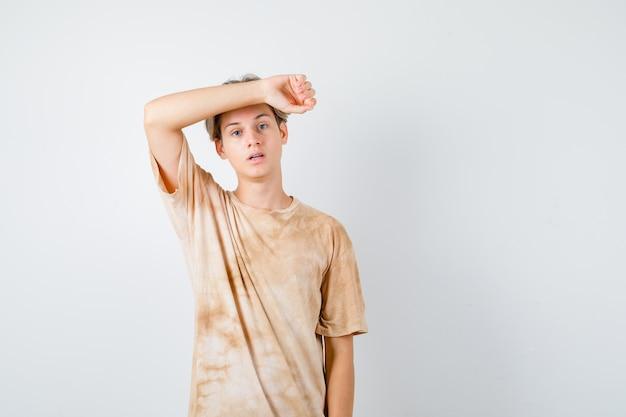 Portret van een jonge tienerjongen die zijn arm op het voorhoofd houdt in een t-shirt en er weemoedig vooraanzicht uitziet