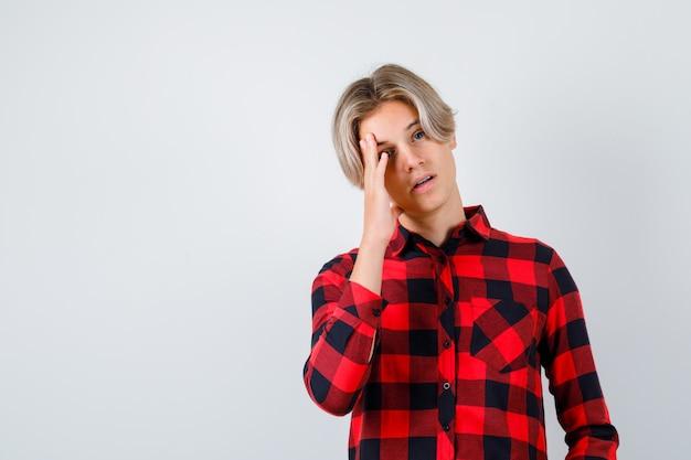 Portret van een jonge tienerjongen die zijn gezicht leunt in een geruit overhemd en een peinzend vooraanzicht kijkt