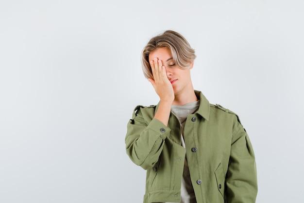 Portret van een jonge tienerjongen die zijn hand op zijn gezicht houdt in t-shirt, jas en vermoeid vooraanzicht kijkt