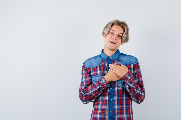 Portret van een jonge tienerjongen die zijn handen op de borst houdt in een geruit hemd en er dankbaar vooraanzicht uitziet