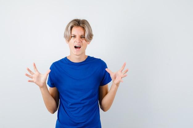 Portret van een jonge tienerjongen die zijn handen op een agressieve manier opheft terwijl hij in een blauw t-shirt schreeuwt en woedend vooraanzicht kijkt