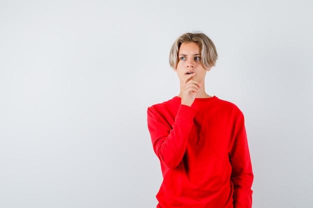 Portret van een jonge tienerjongen met de hand op de kin, wegkijkend in een rode trui en bezorgd vooraanzicht