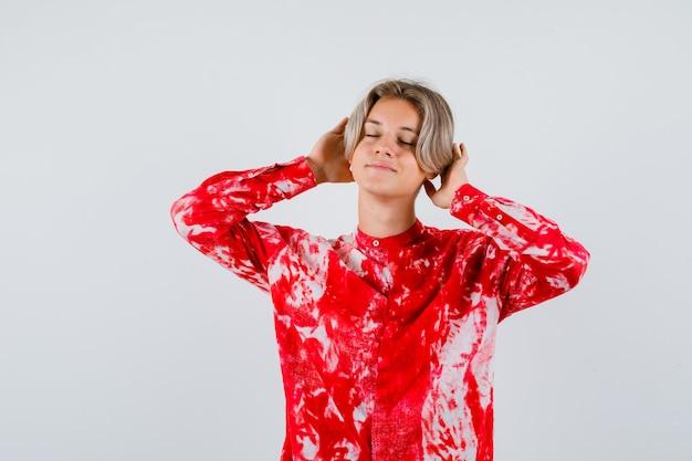 Portret van een jonge tienerjongen met handen achter de oren, ogen dicht in shirt en opgetogen vooraanzicht