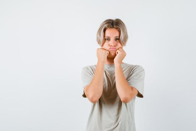 Portret van een jonge tienerjongen mokkend met gezwollen wangen, leunend op handen in een t-shirt en teleurgesteld vooraanzicht