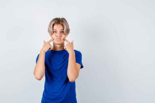 Portret van een jonge tienerjongen wijzend op zijn gezwollen wangen in blauw t-shirt en teleurgesteld vooraanzicht