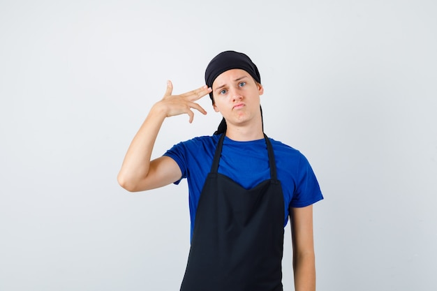 Portret van een jonge tienerkok die zelfmoordgebaar toont in t-shirt, schort en depressief vooraanzicht
