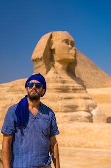 Portret van een jonge toerist gekleed in blauw en een blauwe tulband bij de sfinx van gizeh. caïro, egypte