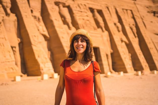 Portret van een jonge toerist in rode jurk die de tempel van nefertari bij abu simbel in het zuiden van egypte in nubië naast het nassermeer bezoekt. tempel van farao ramses ii, reislevensstijl