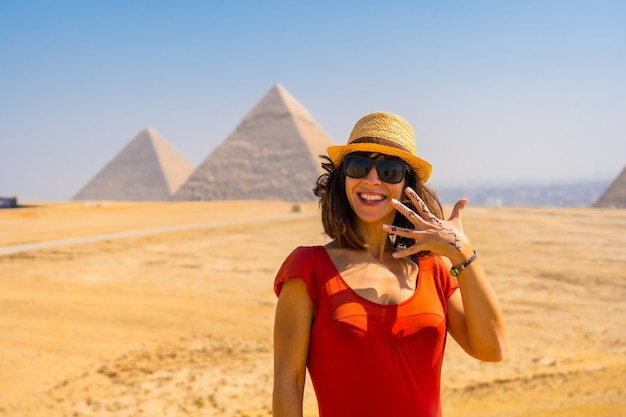 Portret van een jonge toerist in rode jurk die geniet van de piramides van gizeh, het oudste grafmonument ter wereld. in de stad caïro, egypte
