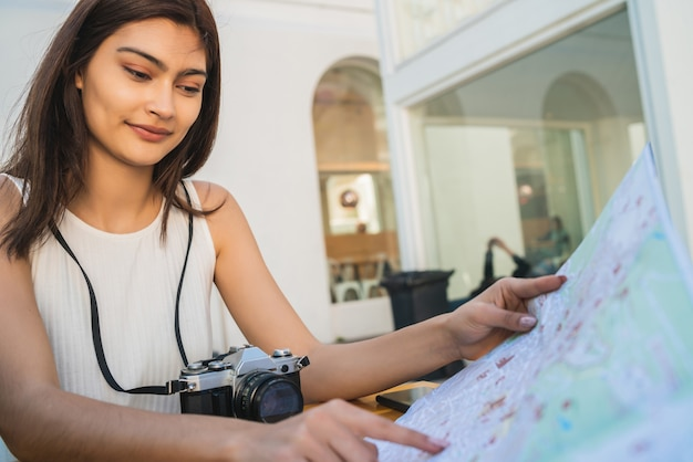 Portret van een jonge toeristische vrouw met een kaart en op zoek naar een routebeschrijving zittend bij coffeeshop. reis concept.