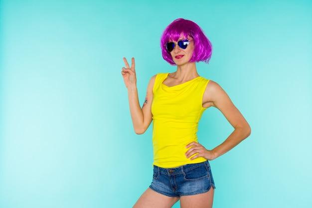 Portret van een jonge transgendervrouw met een probleemhuid in roze pruik en zonnebrilhartvorm op blauwe achtergrond