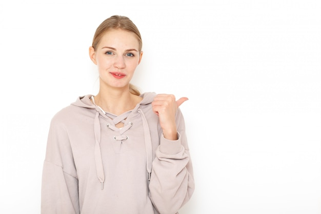 Portret van een jonge triest lachende europese vrouw met blond haar. haar ogen drukken verdriet uit. de duim van haar gebogen linkerhand wijst naar links.