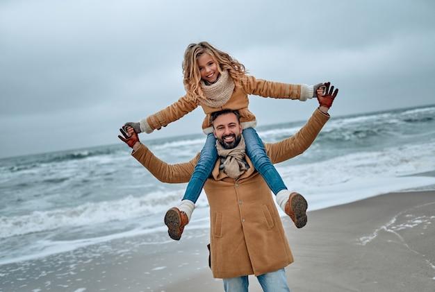 Portret van een jonge vader en zijn schattige dochter die in de winter plezier hebben op het strand.