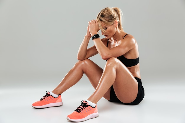 Portret van een jonge vermoeide sportvrouw die terwijl het zitten rust