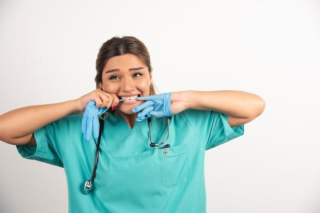 Portret van een jonge verpleegster die medische latexhandschoenen probeert uit te trekken.