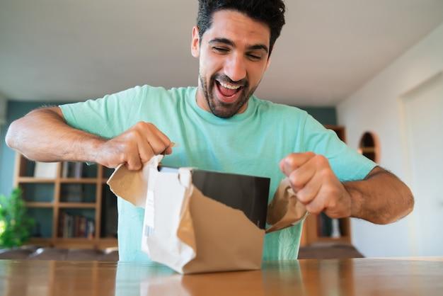 Portret van een jonge verrast man die een geschenkdoos opent terwijl hij thuis op de bank zit. verbaasde en opgewonden man.
