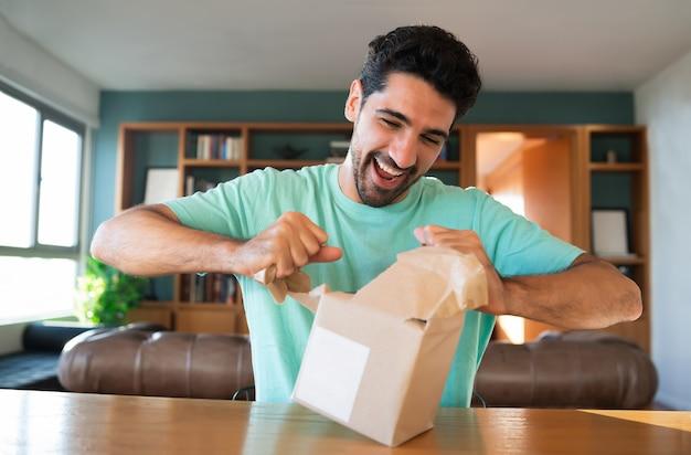Portret van een jonge verrast man die een geschenkdoos opent terwijl hij thuis op de bank zit.