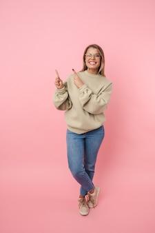Portret van een jonge verraste vrouw in een bril die met de vingers naar boven wijst en geïsoleerd over roze muur knipoogt