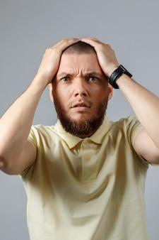 Portret van een jonge verstoorde man in een gele t-shirt met zijn hoofd op grijs.