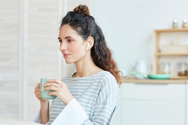 Portret van een jonge volwassen blanke vrouw die 's ochtends thuis thee drinkt en luistert naar muziek in haar draadloze koptelefoon